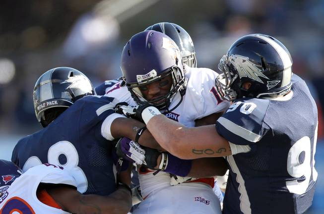Multiple UNR defenders wrap up Northwestern State's Louis Hollier (17) during the first half of the Wolf Pack's 45-34 victory Saturday, Sept. 15, 2012, in Reno.