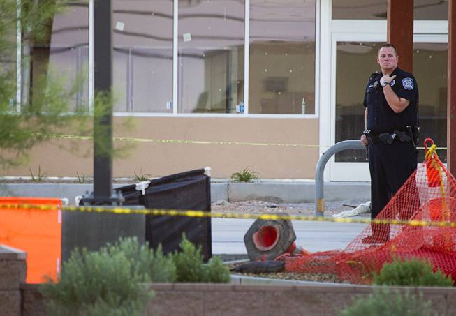 A North Las Vegas Police officer stands near a man's body at the scene of a fatal officer-involved shooting at Martin Luther King Jr. Boulevard and Cheyenne Avenue in North Las Vegas Wednesday, Sept. 19, 2012. The man's body is behind orange and black screens at left.