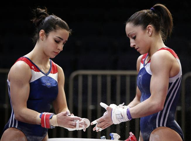 Alexandra Raisman, left, and Jordyn Wieber apply chalk to their hands before practicing on the uneven bars during a training session for Saturday's American Cup gymnastics meet at Madison Square Garden in New York, Friday, March 2, 2012. Wieber, the reigning world champion, is the favorite to win the event again this year.