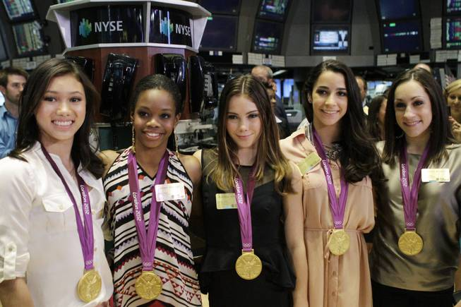 From left, Kyla Ross, Gabby Douglas, McKayla Maroney, Aly Raisman and Jordyn Wieber, members of the U.S. women's Olympic gymnastics gold medal-winning team, pose for photos on the floor of the New York Stock Exchange in New York on Tuesday, Aug. 14, 2012.
