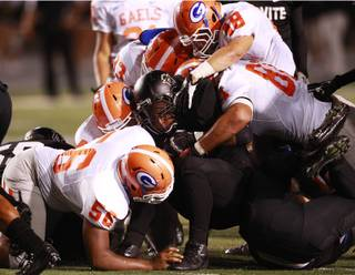 The Bishop Gorman defense stops Servite running back Andrew Moore at the line during their game at Cerritos College in Norwalk, Calif., Friday, Sept. 21, 2012.