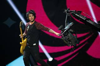 Green Day lead vocalist and guitarist Billie Joe Armstrong grabs a camera during the 2012 iHeartRadio Music Festival at MGM Grand Garden Arena on Friday, Sept. 21, 2012.