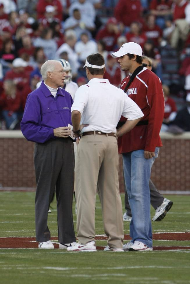 Kansas State head coach Bill Snyder, left, talks with Oklahoma head coach Bob Stoops, center, and quarterback Sam Bradford, right, before an NCAA football game in Norman, Okla. on Saturday, Oct. 31 2009.
