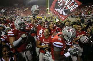 UNLV football players celebrate their first victory of the season, a 38-35 win over Air Force at Sam Boyd Stadium on Saturday night.