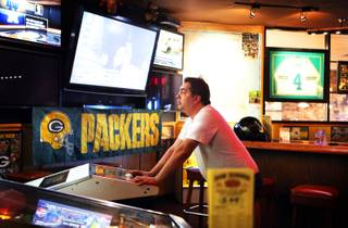 David Taylor of Las Vegas, a Packers fan, plays a golf video game at the Rum Rummer and Badger Cafe, a Wisconsin bar in Las Vegas on Tuesday, September 25, 2012. Taylor said the game last night cost him a parlay ticket.