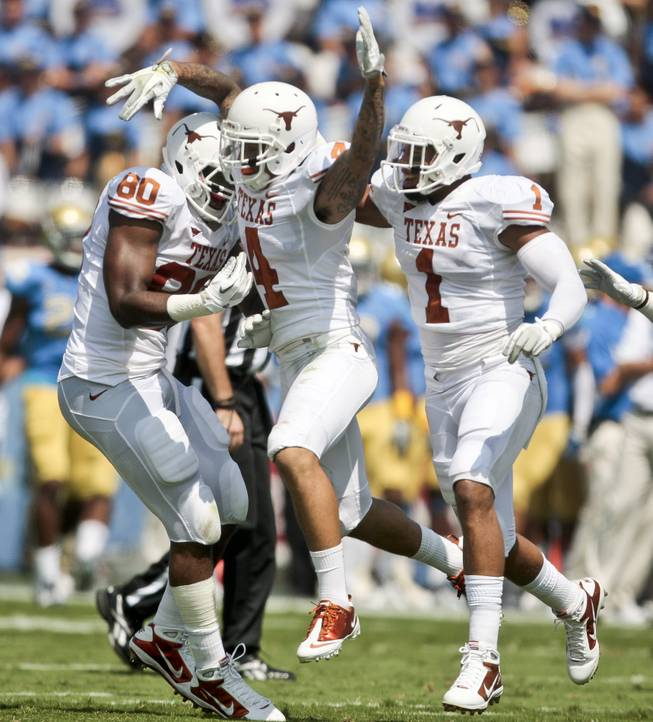 Texas safety Kenny Vaccaro (4) celebrates making an interception off a pass by UCLA quarterback Kevin Prince (4) with teammates Keenan Robinson (1) and Alex Okafor (80) in this file photo.