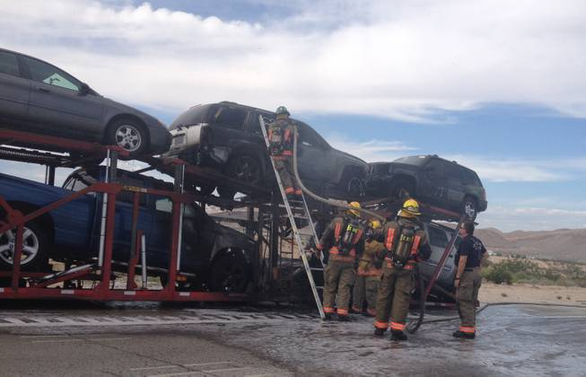 Clark County Fire Department firefighters check over smoldering automobiles that had caught fire on a tractor-trailer Friday afternoon, Sept. 27, on Interstate 15 near the M Resort.