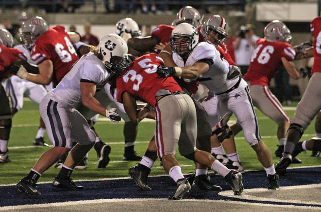 Utah State linebacker Jake Doughty, left, and other Utah State players tackle UNLV running back Tim Cornett (35) for a safety in the fourth quarter of an NCAA college football game Saturday, Sept. 29, 2012, in Logan, Utah. Utah State  defeated UNLV  35-13.   (AP Photo/Rick Bowmer)