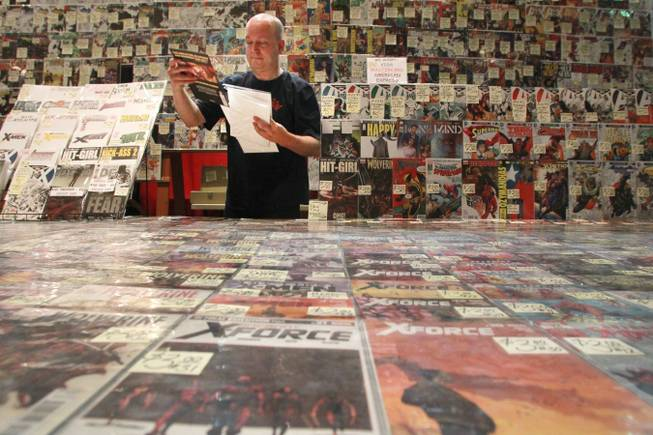A man who declined to give his name bags up a comic book in his store's booth at the Las Vegas Comic Expo Saturday, Sept. 29, 2012.