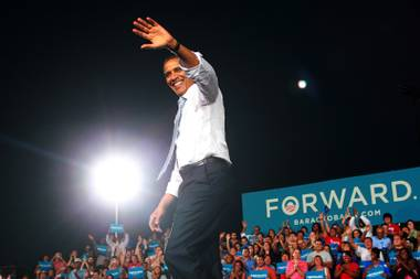 President Barack Obama waves to supporters while arriving at a campaign event Sunday, Sept. 30, 2012 at Desert Pines High School.