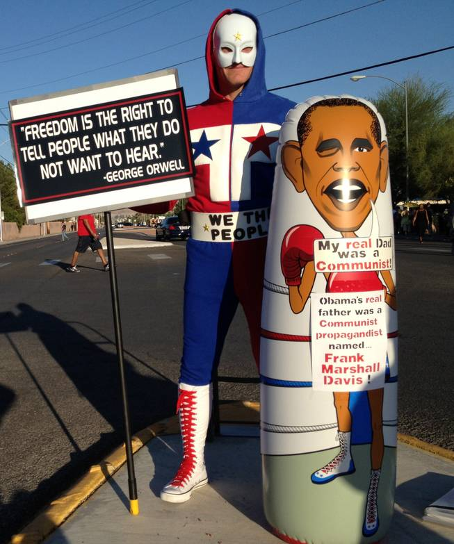 "Richard McCaslin, who goes by ""The Phantom Patriot"" when in costume, protests at a rally for President Barack Obama on Sunday at Desert Pines High School."