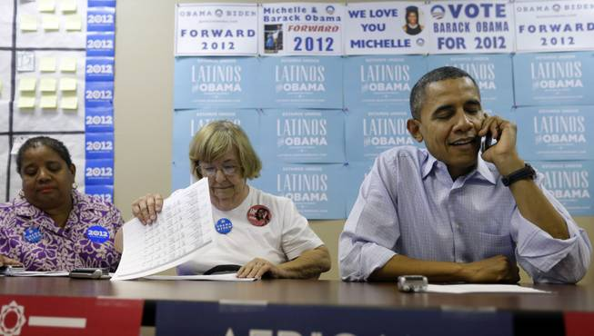 President Barack Obama, right, sits down with volunteers to make phone calls to supporters during a visit to a local campaign office, Monday, Oct. 1, 2012 in Henderson, Nev.