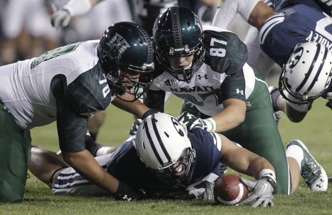 A Brigham Young player dives onto a fumble as Hawaii offensive linesman Frank Loyd Jr. (70) and tight end Ryan Hall (87) watch during the third quarter of an NCAA college football game Friday, Sept. 28, 2012, in Provo, Utah.