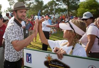 Justin Timberlake gives a high-five to standard bearer Annick Haczkiewicz, 12, during the Pro-Am portion of the Justin Timberlake Shriners Hospitals for Children Open at TPC Summerlin Wednesday, Oct. 3 2012.