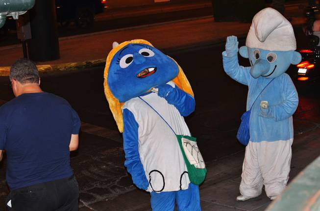 A performer's mustache is seen underneath his Smurfette costume as he leans back to scratch his neck while another performer in a smurf costume is seen greeting a passerby while holding his money September 2012.
