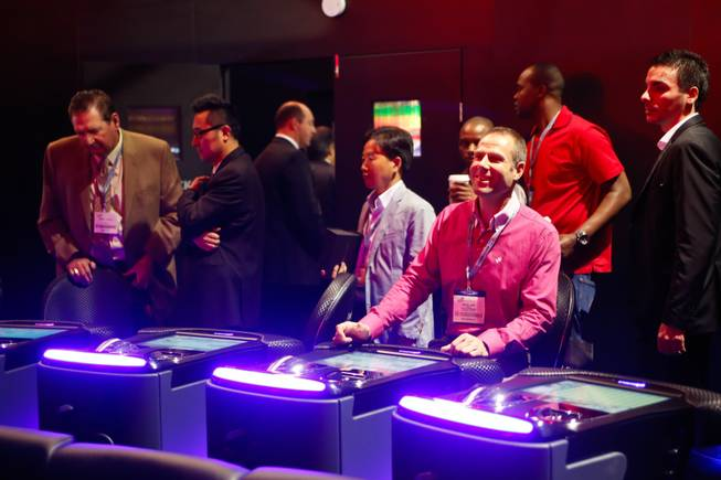 An exhibitor plays a round of Keno on Interblock's electronic gaming machine and watches the results on a life-size holographic display, Thursday Oct. 4, 2012.