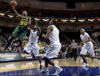 Baylor's Pierre Jackson (55) goes up for a shot against West Virginia's Jabarie Hinds (4), Kevin Jones (5) and Dominique Rutledge (1) in the second half of an NCAA college basketball game, Friday, Dec. 23, 2011, in Las Vegas. Baylor won 83-81 in overtime.