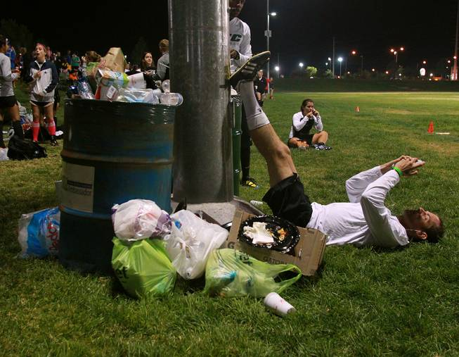 Next to the detritus of the day, OSC player Ben Kozy from Washington D.C. puts his legs up while listening to music before their championship game during the World Adult Kickball Association Founders Cup Saturday, Oct. 6, 2012.