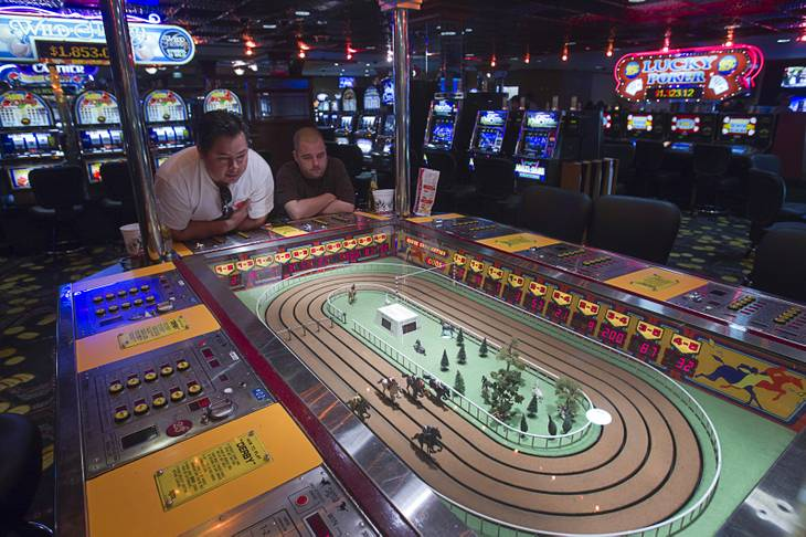 "Jose Halse, left, and John Pecor of San Diego try out a Sigma Derby game on a ""Vintage Vegas"" casino floor at the D Las Vegas in downtown Las Vegas Tuesday, Oct. 9, 2012. The casino had to reapply to have the game approved in Nevada because the original approval had expired, said CEO Derek Stevens. The casino, formerly Fitzgeralds, is celebrating it's rebranding and renovation with festivities this weekend."