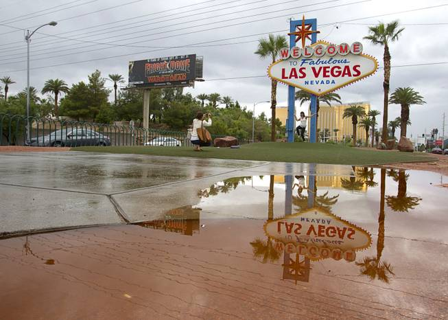"The ""Welcome to Las Vegas""  sign is reflected in a rain puddle as Amanda Thompson photographs her sister Melinda Casey Thursday, Oct. 11, 2012. Thompson is living in England and Casey is from Australia so they decided to meet halfway for a Vegas vacation, they said."