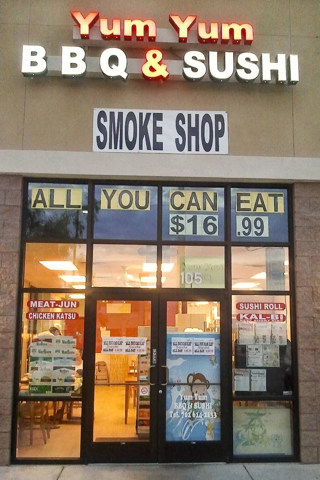 The store front of the Yum Yum BBQ & Sushi restaurant advertises their all you can eat sushi and smoke shop cigarette brands.