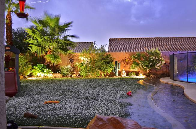 A backyard in Henderson is illuminated by lightning amid a thunderstorm late Thursday, Oct. 11, 2012. Hail was reported in various parts of Henderson; its accumulation is seen on the grass.