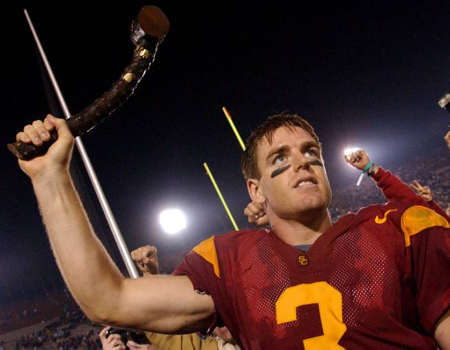 In this Nov. 30, 2002, AP file photo, Southern California quarterback Carson Palmer holds up the Jeweled Shillelagh to celebrate USC's 44-13 win against Notre Dame in an NCAA college football game in Los Angeles. For each USC victory a Trojan head with a ruby is attached and for each Irish victory, an emerald-studded shamrock is attached  — making it one expensive club.