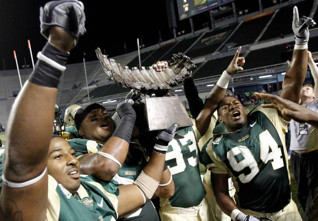 UAB linebacker Jestin Williams (56), and teammates Greg Calhoun (64), Andrew Mahan (93), and Bryant Turner (94) celebrate holding the Bones trophy after beating Memphis 31-15 during the second half of an NCAA college football game on Saturday, Nov. 20, 2010, in Birmingham, Ala.