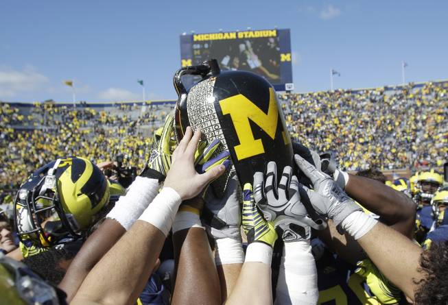 Michigan football players hold the Little Brown Jug after defeating Minnesota 58-0 during a college football game in Ann Arbor, Mich., Saturday, Oct. 1, 2011. Michigan kept the jug, the oldest trophy game in major college football that dates to 1909.