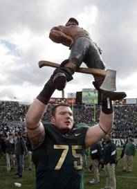 Michigan State offensive tackle Jared McGaha (75) holds the Paul Bunyan Trophy after the Spartans defeated Michigan 28-14 in an NCAA college football game in East Lansing, Mich., Saturday, Oct. 15, 2011. The college rivalry trophy is awarded to the winner of the football game between Michigan and Michigan State.