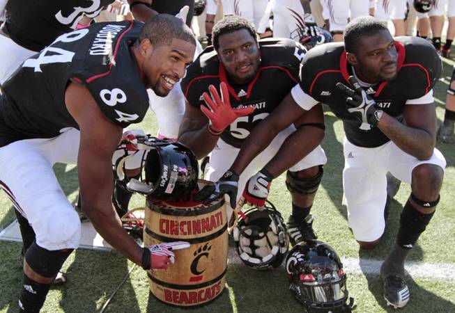Cincinnati players Orion Woodard (84), Randy Martinez, center, and Kenbrell Thompkins celebrate with the Keg of Nails trophy in the closing seconds of their 25-16 win over Louisville in an NCAA college football game, Saturday, Oct. 15, 2011, in Cincinnati. Cincinnati has won five straight games in the rivalry that dates back to 1929.