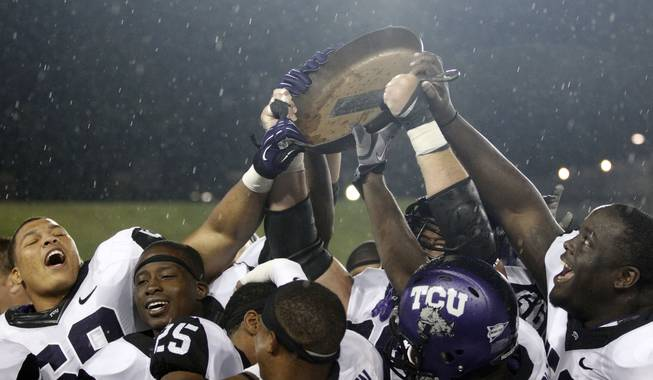 "Members of the TCU football team reach in to touch the ""Iron Skillet,"" their prize for beating SMU in an NCAA college football game on Saturday, Sept. 29, 2012, in Dallas. TCU won 24-16."