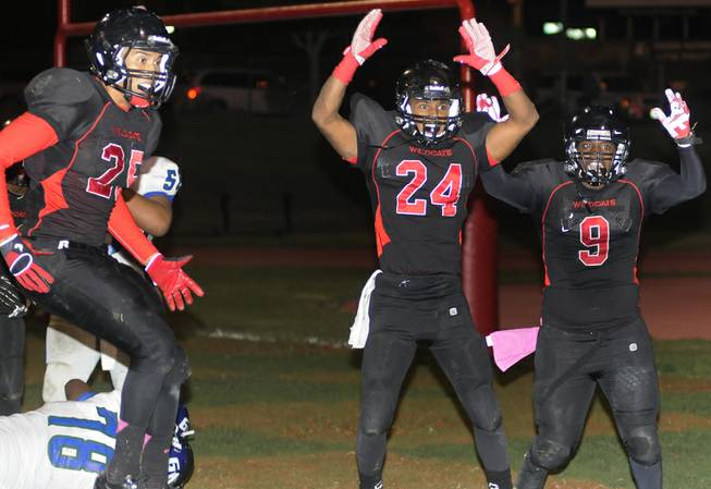 Wildcat defensive players Angel Perez (25), Chritian Slack (24), and D'Anthony Wade (9) celebrate as they signal touchdown after Las Vegas recovered a Green Valley fumble for a defensive score during the first half of play at Las Vegas High on Friday night.