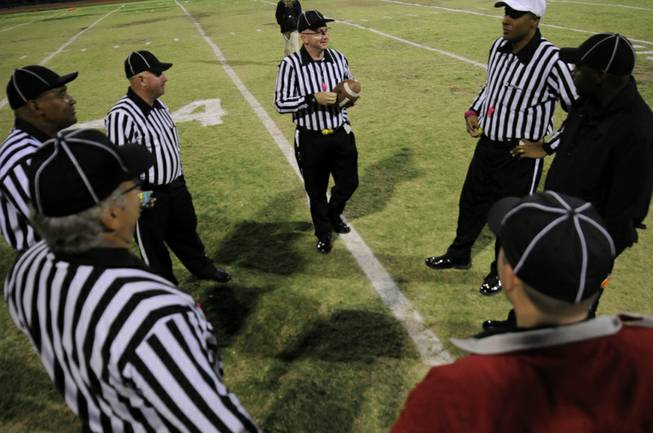 The officiating crew for the game between the visiting Gators and the Wildcats have a pre-game huddle at mid-field on Friday night at Las Vegas High School.