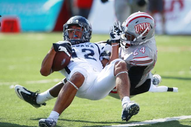UNLV defensive back Fred Wilson tackles UNR wide receiver Richy Turner during their game Saturday, Oct. 13, 2012 at Sam Boyd Stadium. UNR came from behind and won the game, for the eighth consecutive time, 42-37.