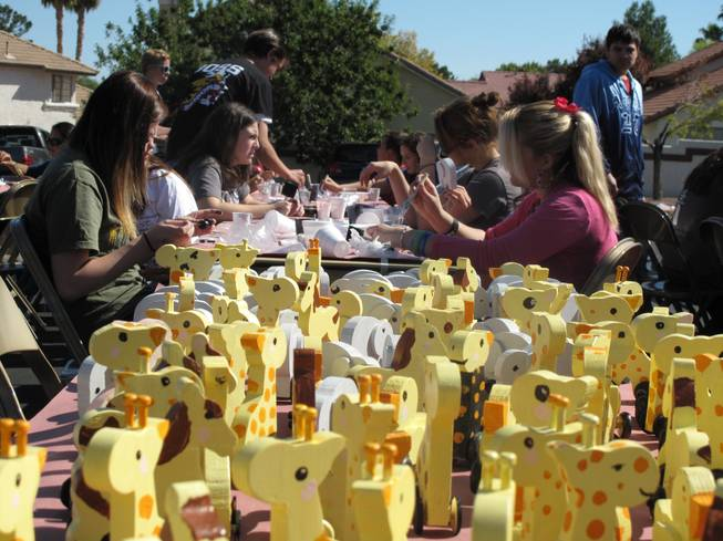A group of teenagers paint and assemble wooden toy giraffes and elephants among other animals that will then be donated to charity as part of their Church of Jesus Christ of Latter-day Saints Day of Service community project on Saturday.