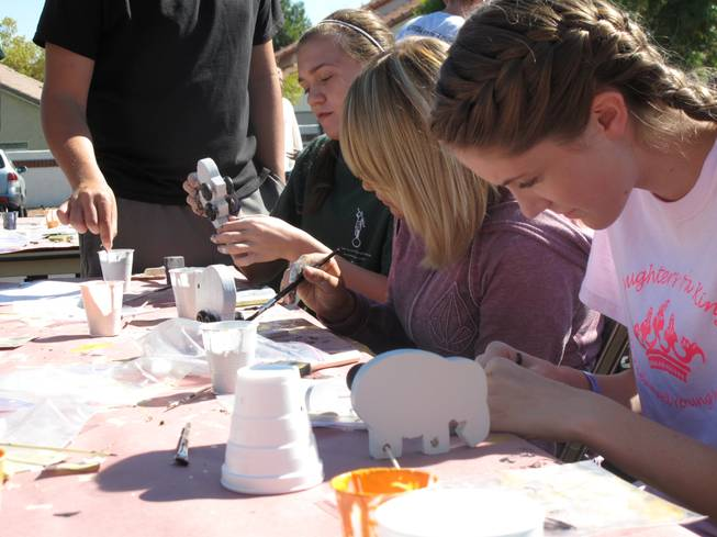 Teens at the Green Valley Church of Jesus Christ of Latter-day Saints assemble wooden toys to be donated to charity for their Day of Service community project on Saturday.