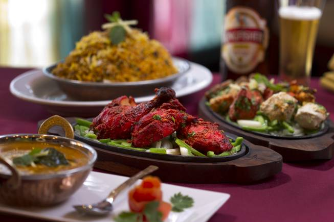 Tandoori chicken, center, at Saffron Flavors of India restaurant, 4450 N. Tenaya Way, Sunday, Oct. 14, 2012. Also pictured, clockwise from top right, Saffron biryabi, a mixed Saffron platter, and Chicken Madras curry.