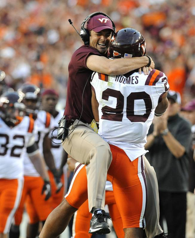 Virginia Tech assistant coach Shane Beamer leaps into the arms of his running back Michael Holmes after Holmes scored a touchdown to give Virginia Tech a 17-13 lead over Cincinnati during an NCAA college football game, Saturday, Sept. 29, 2012, in Landover, Md. Cincinnati defeated Virginia Tech 27-24.