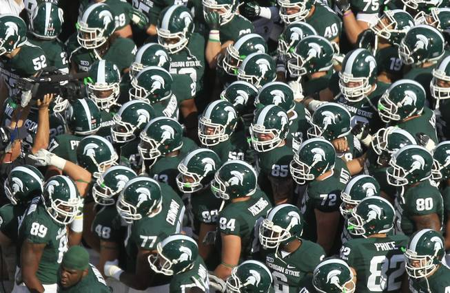 The Michigan State football team meets at midfield before during the first quarter of an NCAA college football game Ohio State at Spartan Stadium in East Lansing, Mich., Saturday, Sept. 29, 2012.