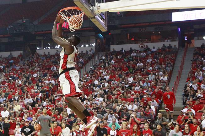 UNLV guard Katin Reinhardt, in red shirt standing on steps on the right, watches as forward Anthony Bennett reverse dunks a pass thrown from Reinhardt during the slam dunk portion of UNLV's First Look scrimmage Thursday, Oct 18, 2012.