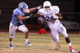 Chance McCutcheon, left, of Centennial reaches to tackle Nathan Starks of Bishop Gorman during their game at Centennial High School in Las Vegas on Friday, October 19, 2012.