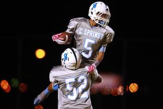 Canyon Springs lineman Alonzo Pittman lifts running back D.J. Pumphry into the air after a touchdown.