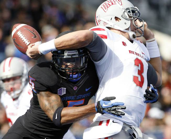 Boise State's Jamar Taylor hits UNLV quarterback Nick Sherry, causing Sherry to lose the ball Saturday, Oct. 20, 2012, in Boise, Idaho.