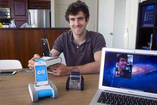 Keller Rinaudo, one of the three Romotive founders, poses  with the new Romo smartphone robot at the Romotive offices in downtown Las Vegas Wednesday, Oct. 24, 2012.  The original model is at center. The new Romo can be controlled over the Internet. Rinaudo's face, captured by the Romo in his hands, is shown on the computer screen at right. The new Romo with enhanced features can be ordered on kickstarter.com and is featured in the Neiman Marcus Holiday catalog.