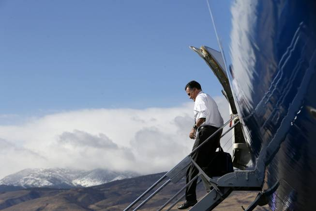 With the Reno Mountains in the background, Republican presidential candidate, former Massachusetts Gov. Mitt Romney steps off his campaign plane at Reno-Tahoe International Airport in Reno, Nev., Wednesday, Oct. 24, 2012, before traveling to a campaign rally at the Reno Events Center.
