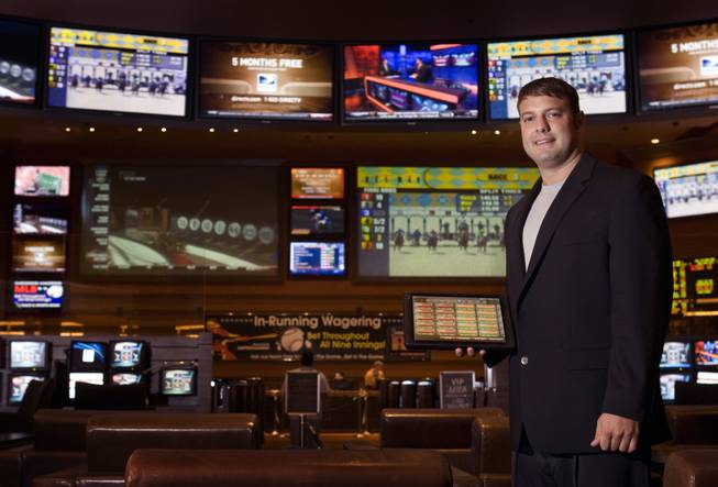 "Race and sports book director Mike Colbert poses with a wireless tablet at the M Resort on Wednesday, Aug. 4, 2010. Customers with accounts can use the tablet to place bets without standing in line. The sports book also has ""In-Running"" wagering during games."