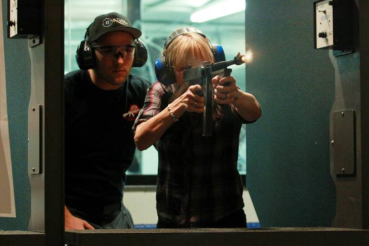 Lisa Gatewood fires a Thompson submachine gun at the Guns and Ammo Garage Oct. 25, 2012.