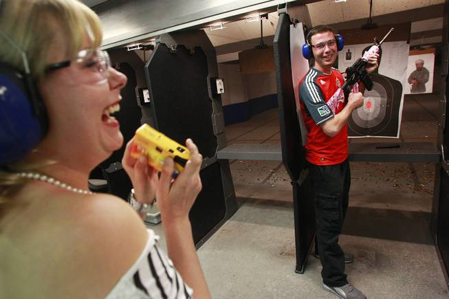 Roxie Jekosz laughs while her boyfriend Matthew Cook poses with a machine gun at the Guns and Ammo Garage Oct. 25, 2012.