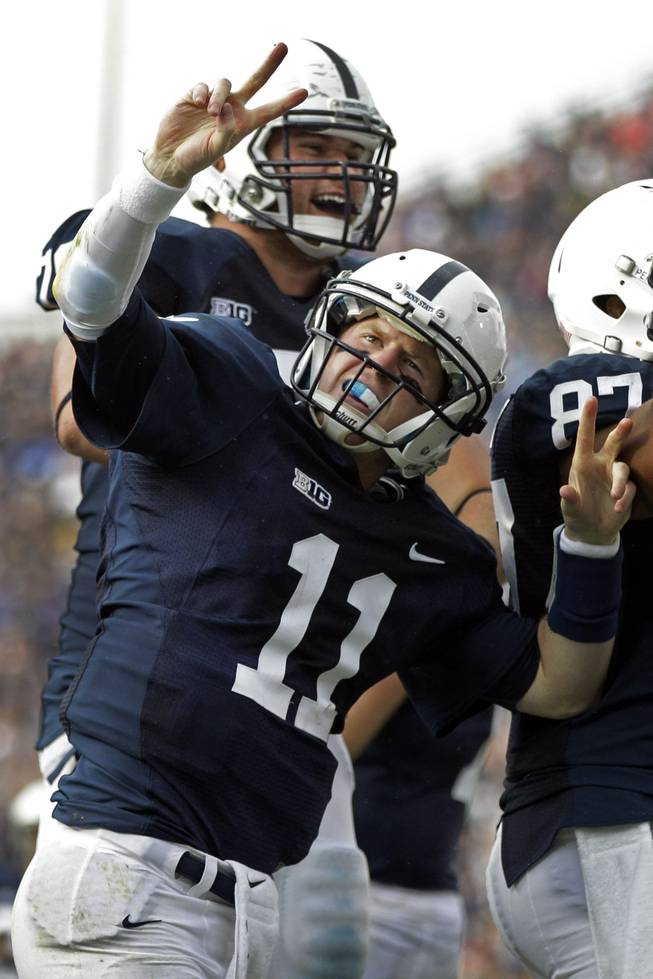 Penn State quarterback Matthew McGloin (11) and Penn State offensive tackle Mike Farrell, rear, celebrate McGloin's rushing touchdown during the second quarter of an NCAA college football game against Temple in State College, Pa., Saturday, Sept. 22, 2012.